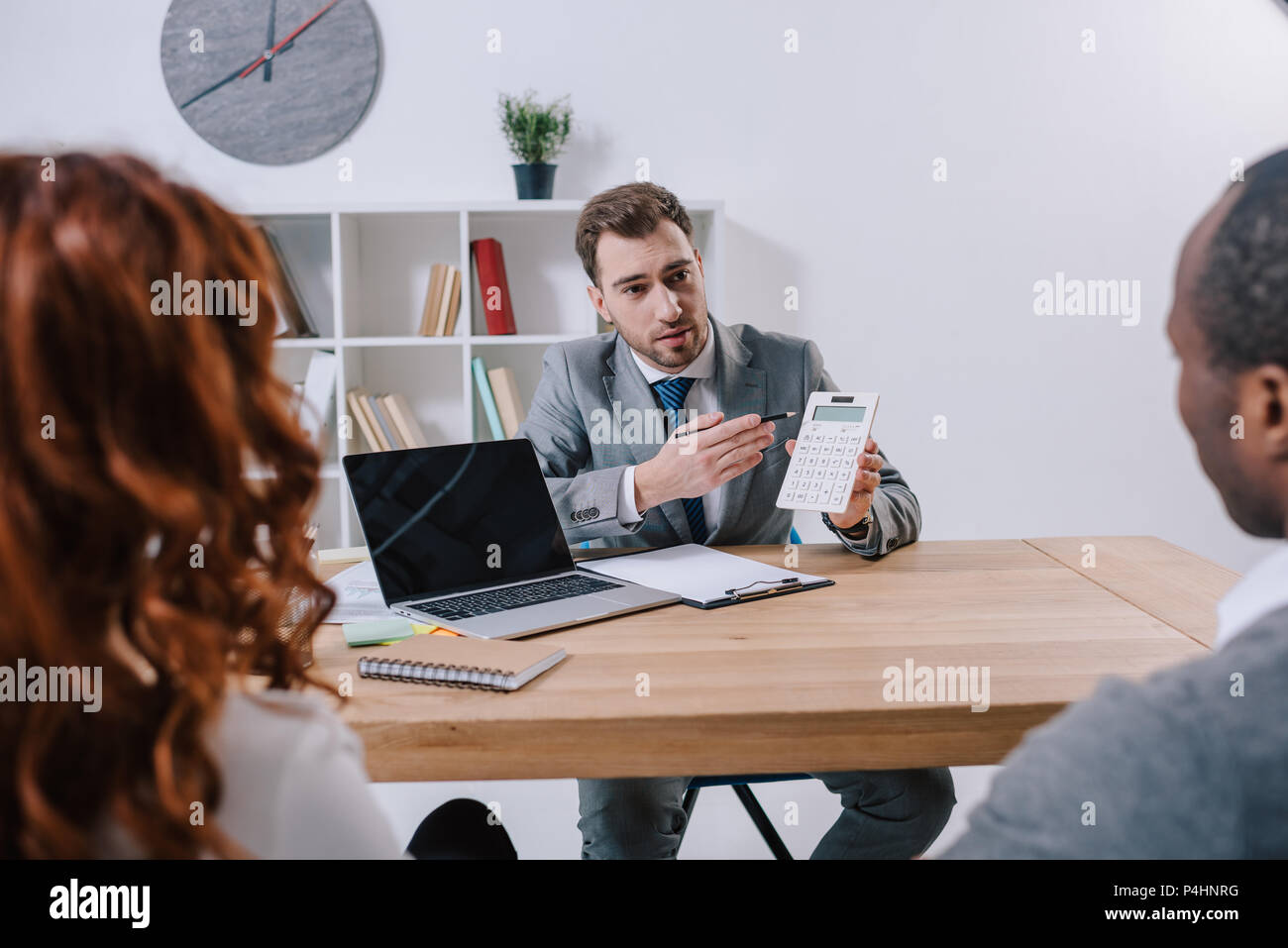 Financial adviser showing calculation while clients sitting at table with laptop - Stock Image