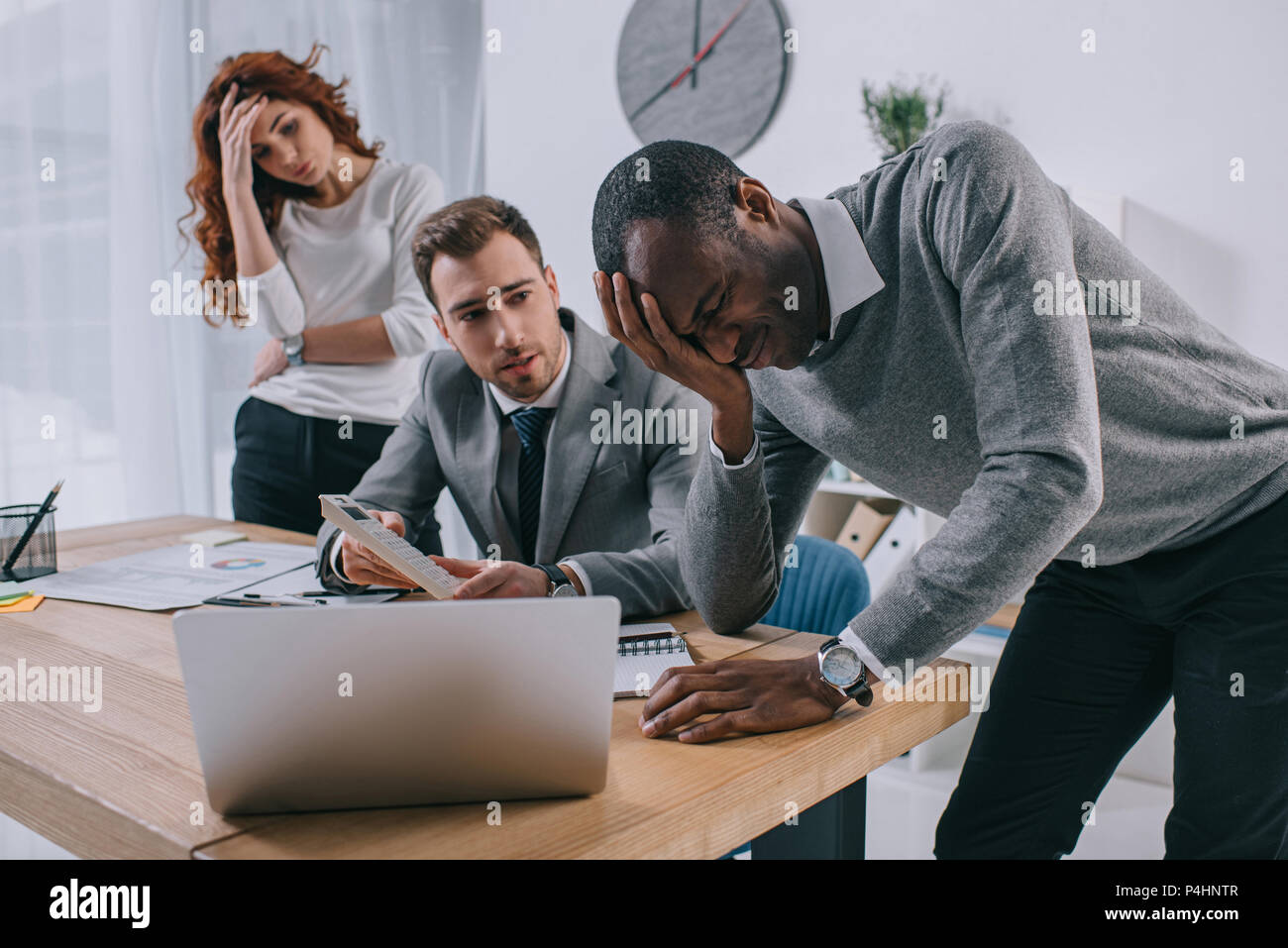 Financial adviser showing calculation to upset business partners - Stock Image