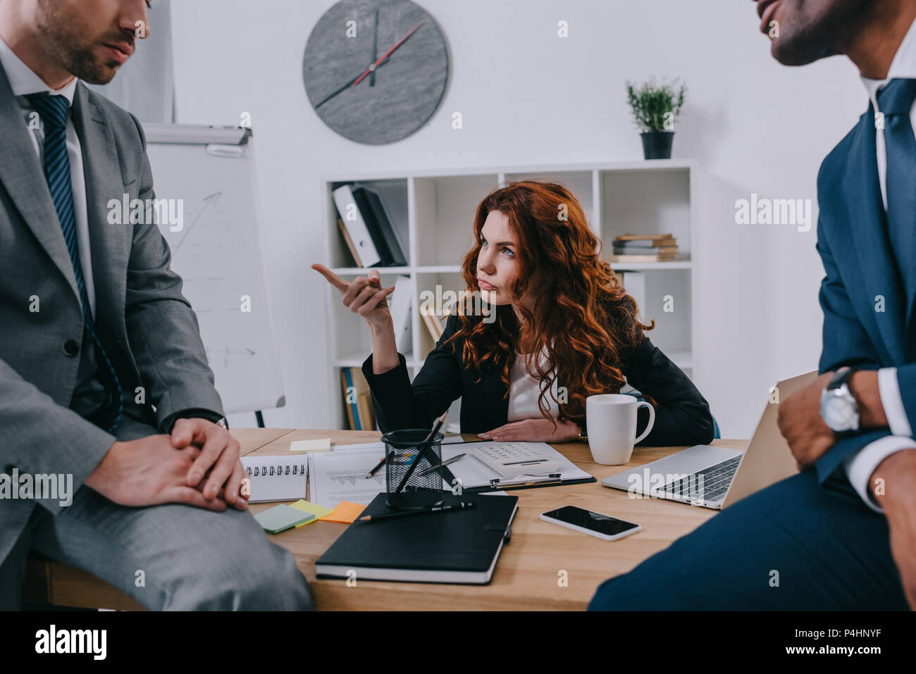 Cropped view of two businessmen sitting on table and manager pointing by finger Stock Photo