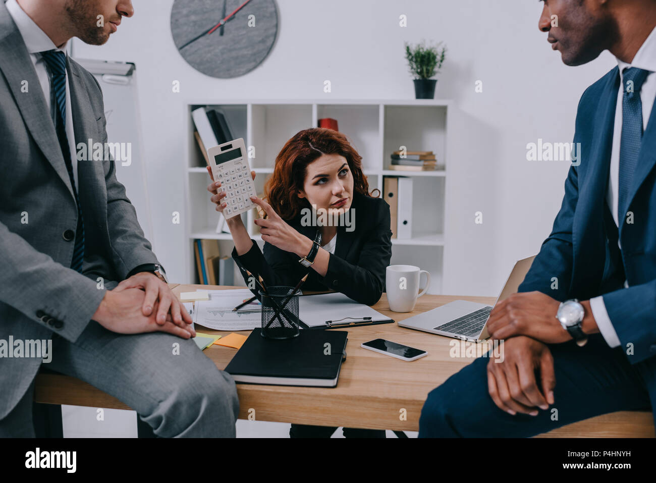 Investment adviser showing calculation to businessmen - Stock Image