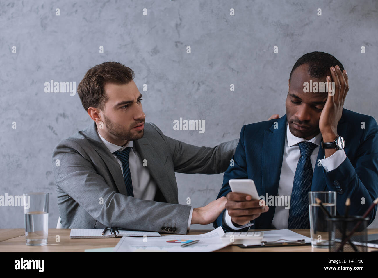 Young stylish businessman cheering up upset partner with smartphone in hand - Stock Image