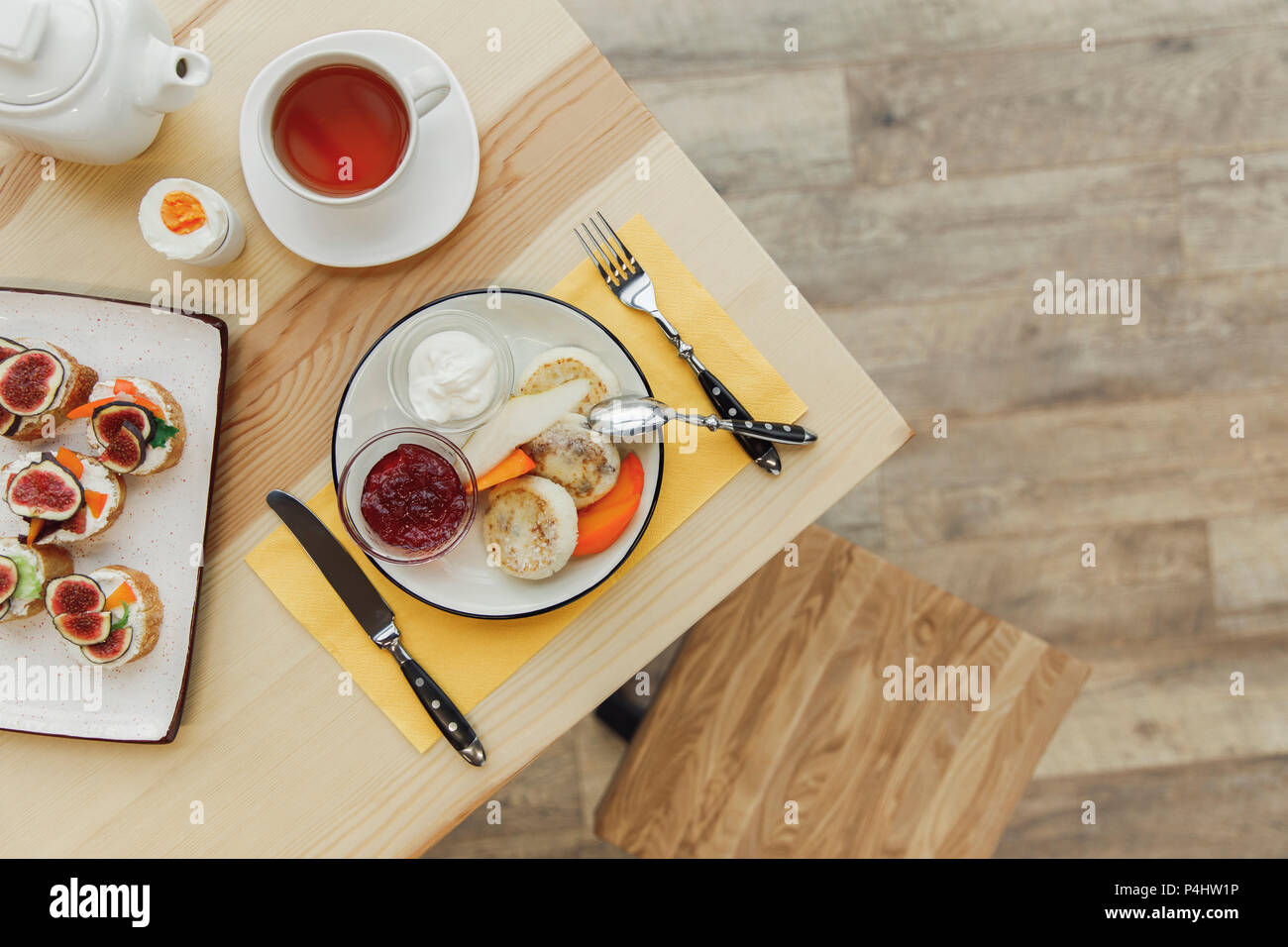top view of tasty healthy breakfast with tea set on wooden table - Stock Image