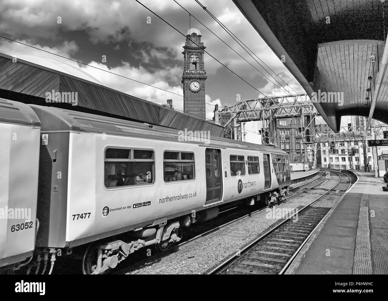Mono image of Delayed Electric Northern Railway EMU train at Manchester Oxford Road Railway station, North West England, UK, back to the 1970s - Stock Image