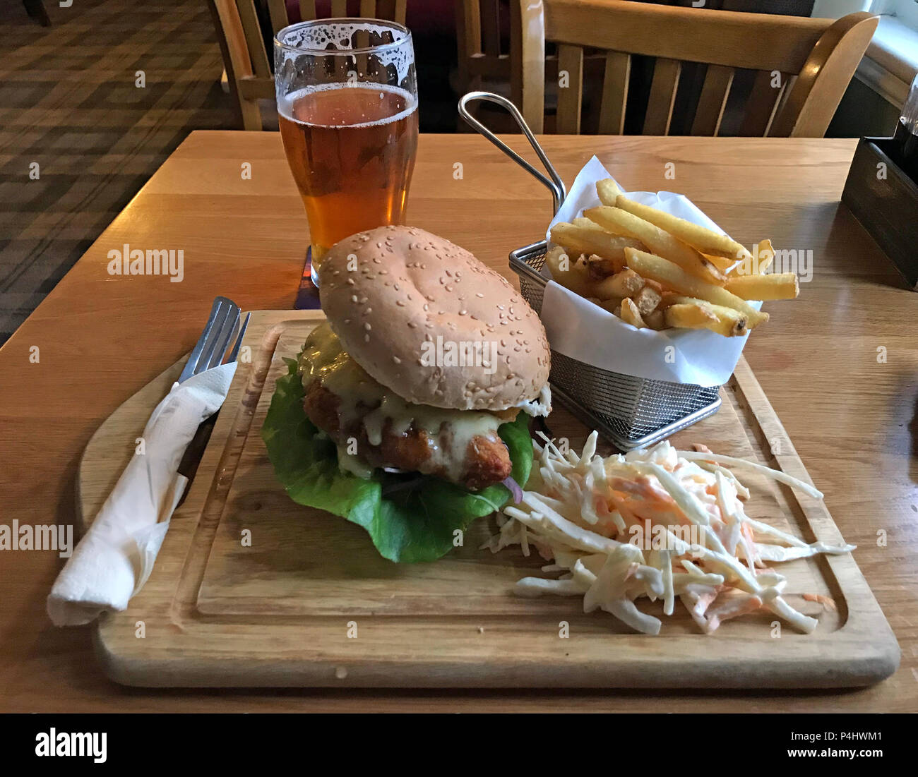 Chicken Burger meal with fries, coleslaw, and a pint in a traditional English pub, Somerset, South West England, UK Stock Photo