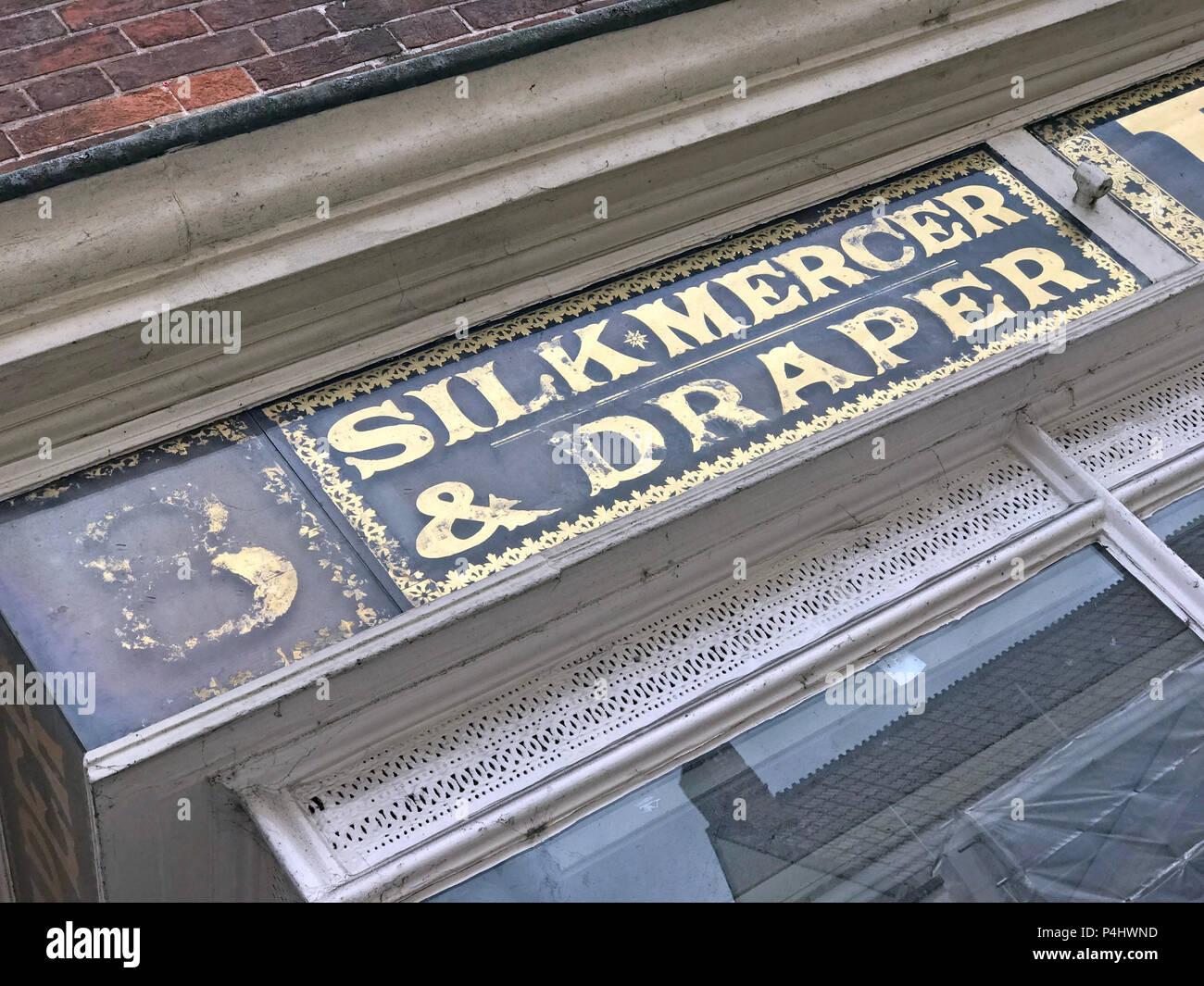 EH Hooper, Silk Mercer & Draper, Millinery & Mantles shop sign in gold lettering, 25 High Street, Bridgwater, Somerset, England, UK, TA6 3BE - Stock Image