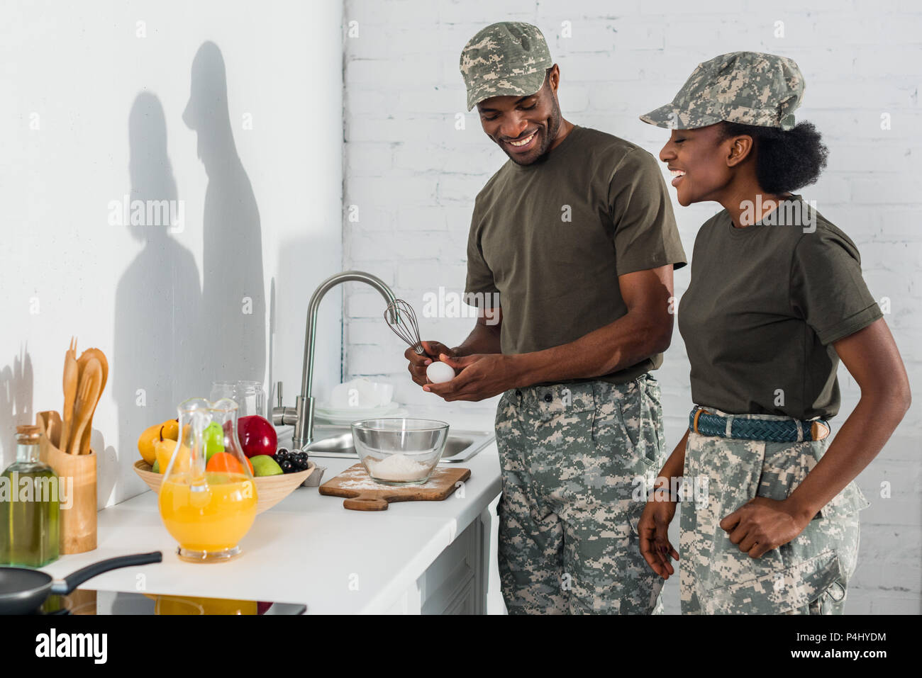Couple of soldiers cooking together at home kitchen - Stock Image