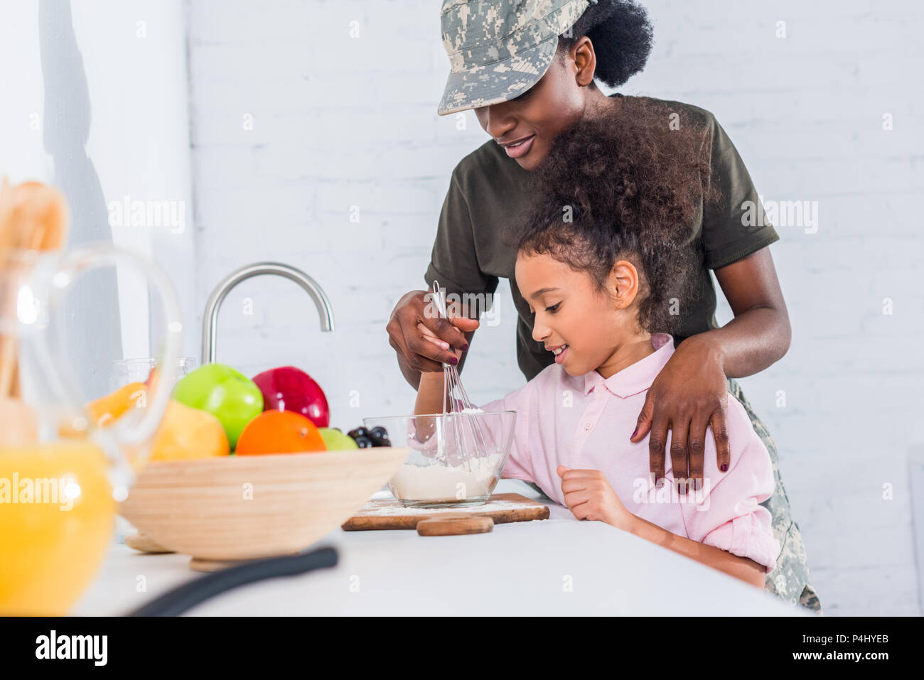 African american soldier with little daughter cooking together at home kitchen - Stock Image