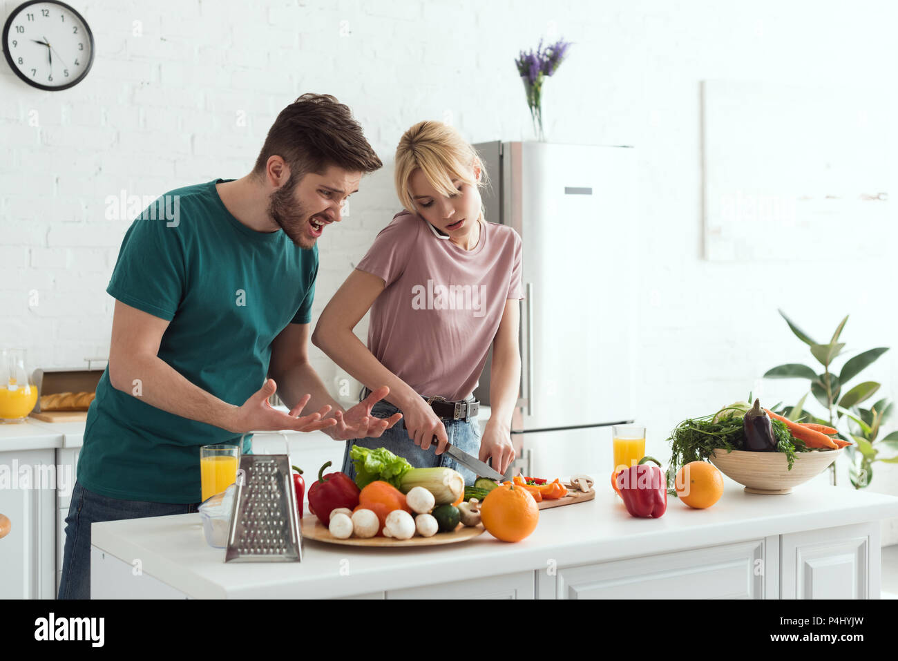 boyfriend grimacing while girlfriend cooking and talking by smartphone at kitchen - Stock Image