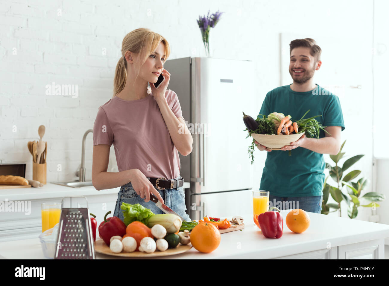 vegan girlfriend talking by smartphone while cooking at kitchen - Stock Image