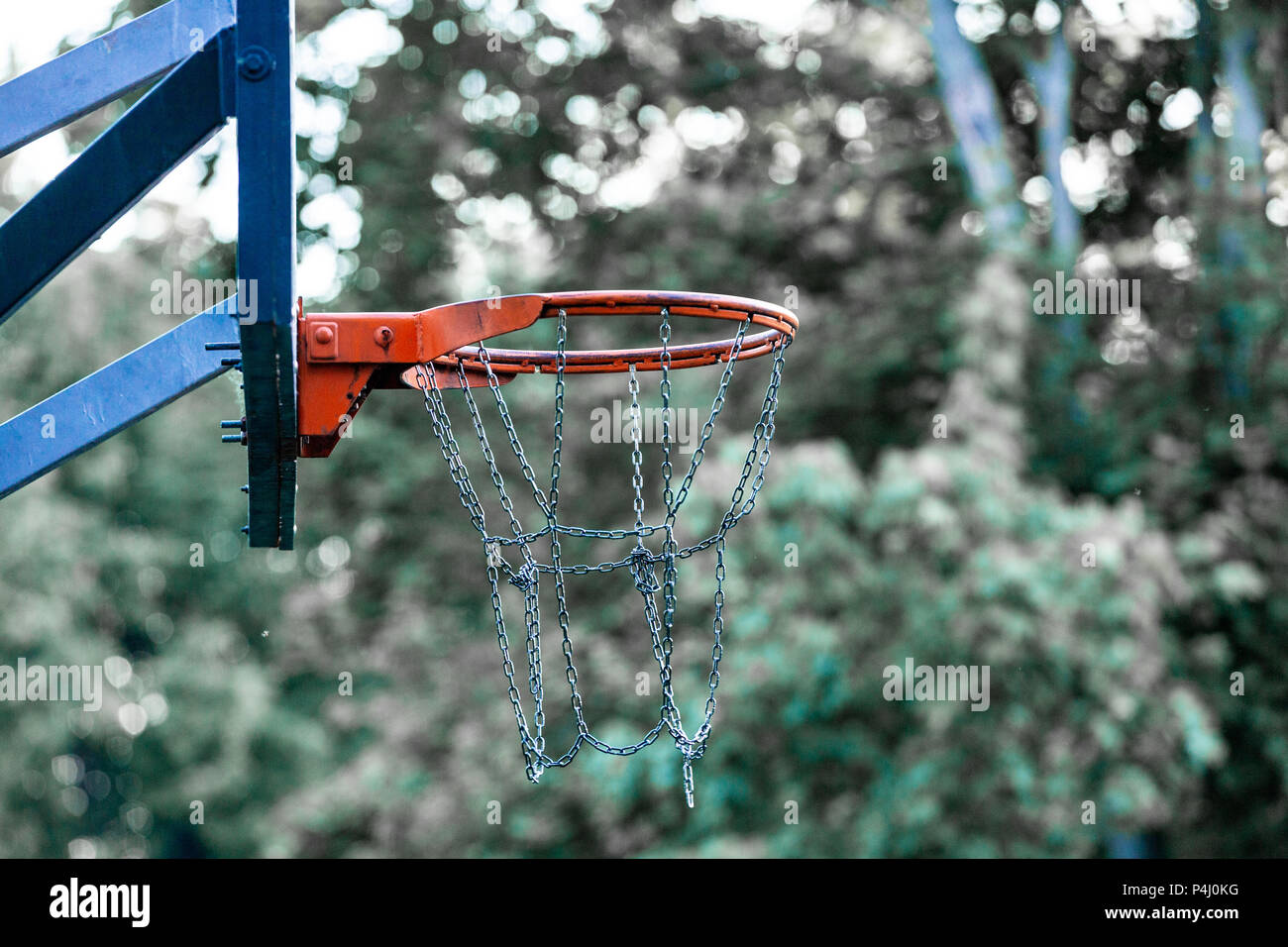 Picture of a basketball field goal with the trees in background. - Stock Image