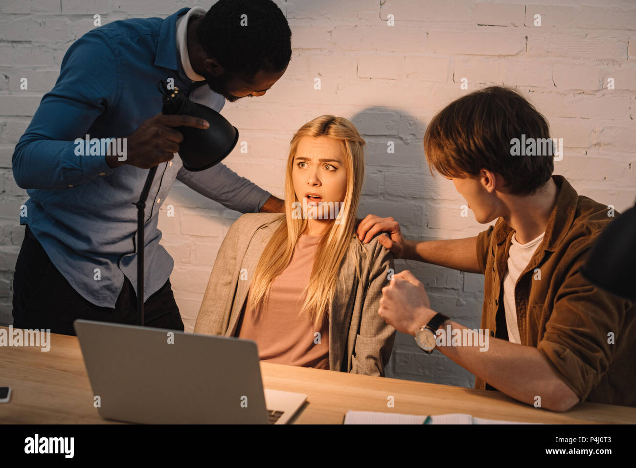 two multicultural businessmen threatening and shine lamp in face of businesswoman - Stock Image