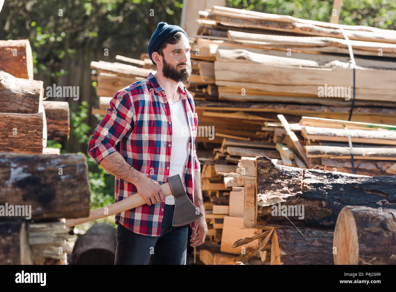 3faa2920574 bearded lumberjack in checkered shirt standing with axe at sawmill ...