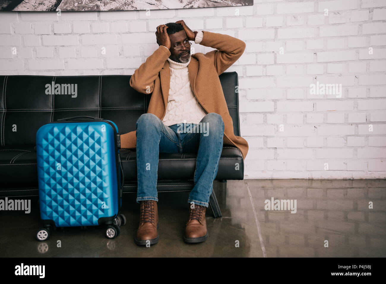 Middle aged traveler sitting on a sofa and clutching head - Stock Image
