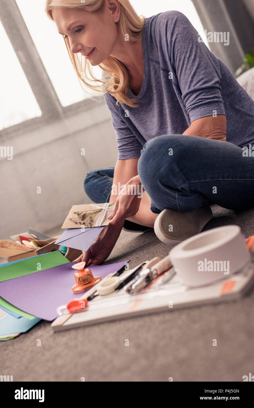 smiling blonde woman paper crafting at home Stock Photo