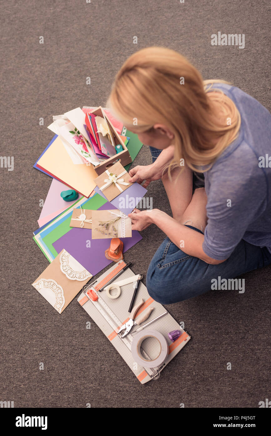 overhead view of blonde woman paper crafting at home - Stock Image