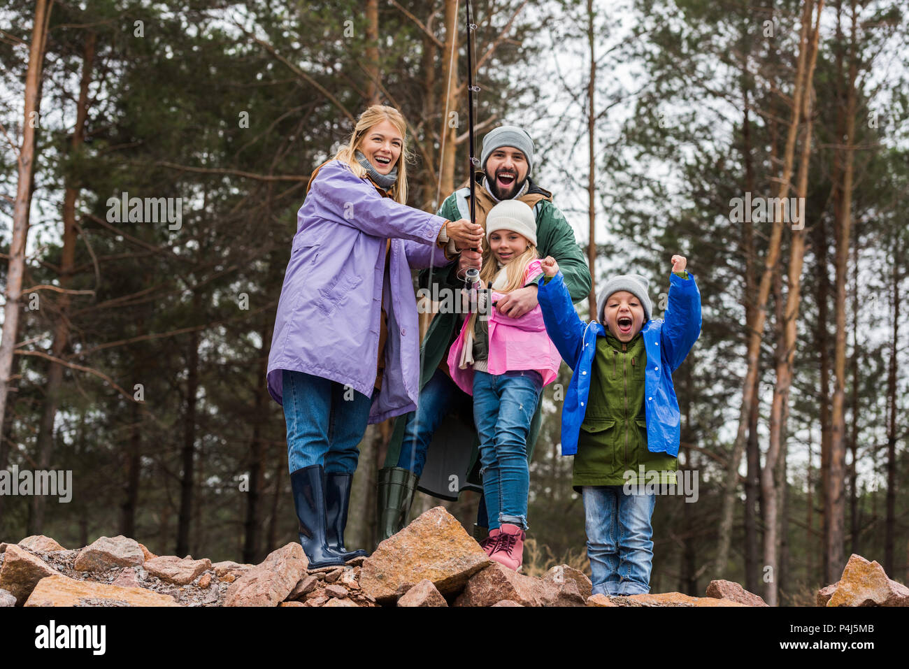 happy young family fishing together at forest lake - Stock Image