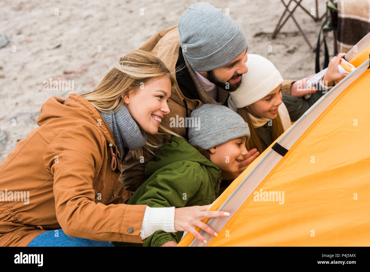 beautiful young family looking at camping tent - Stock Image