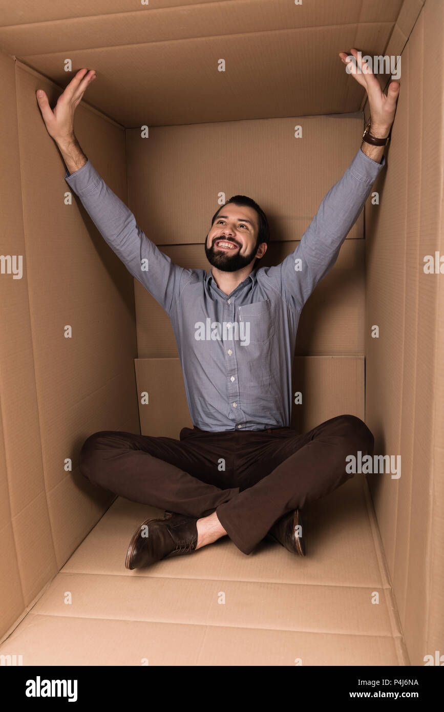 cheerful man sitting in cardboard box, introvert concept - Stock Image