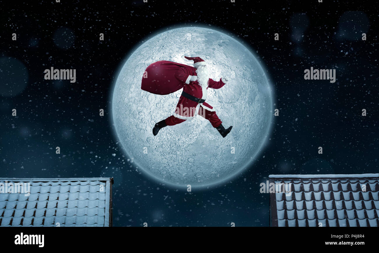Santa Claus jumping between rooftops at night with bag full of gifts - Stock Image