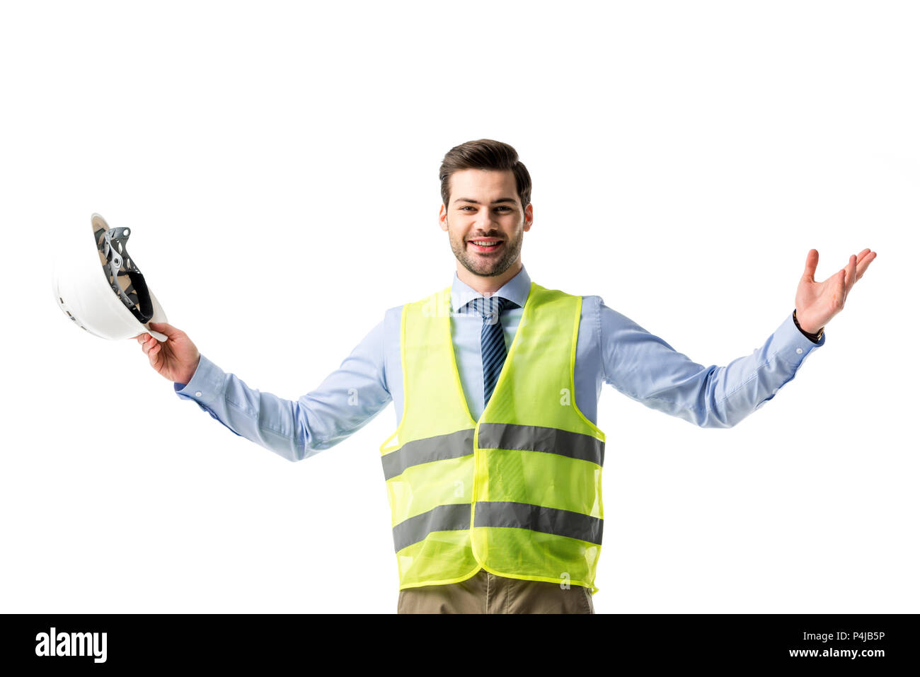 Smiling man in reflective vest holding hardhat isolated on white - Stock Image