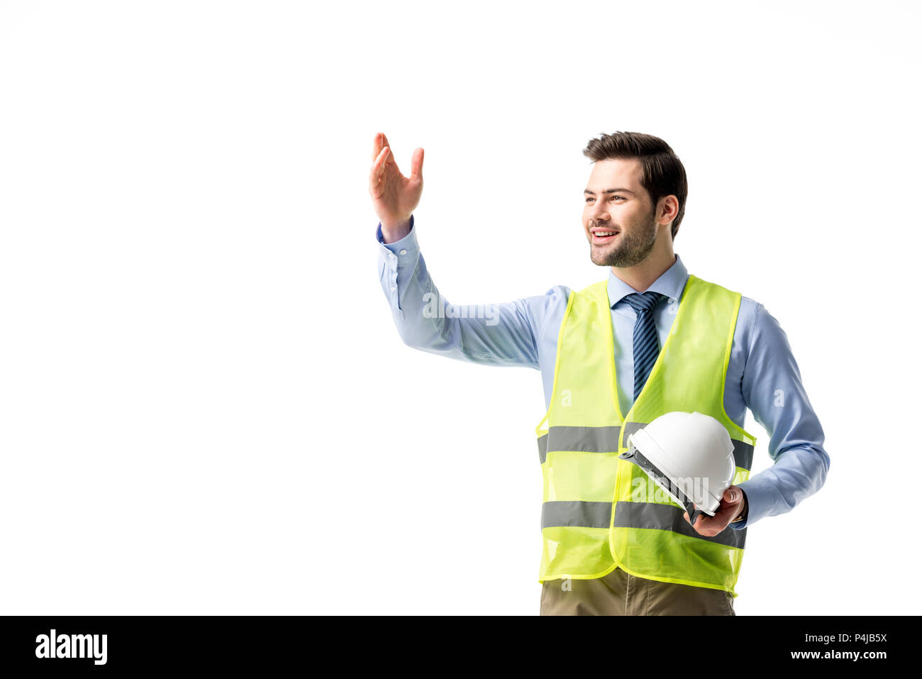Architect in reflective vest holding hardhat isolated on white - Stock Image