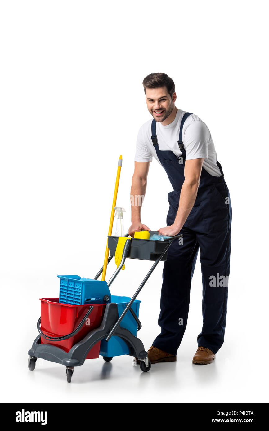 smiling cleaner in uniform with cart isolated on white - Stock Image