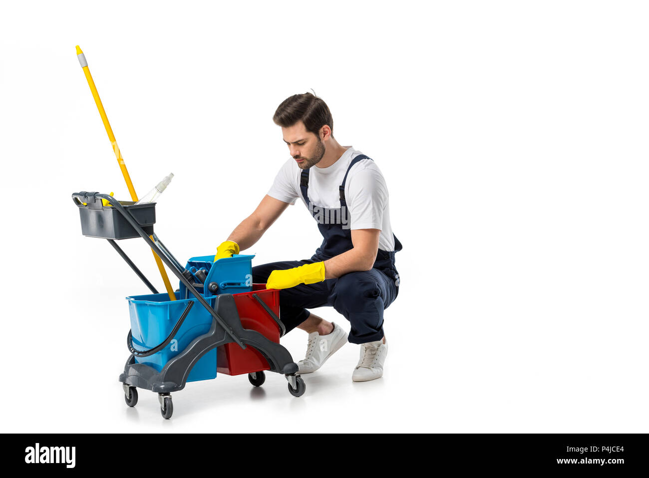 cleaner in uniform and rubber gloves with cart isolated on white - Stock Image