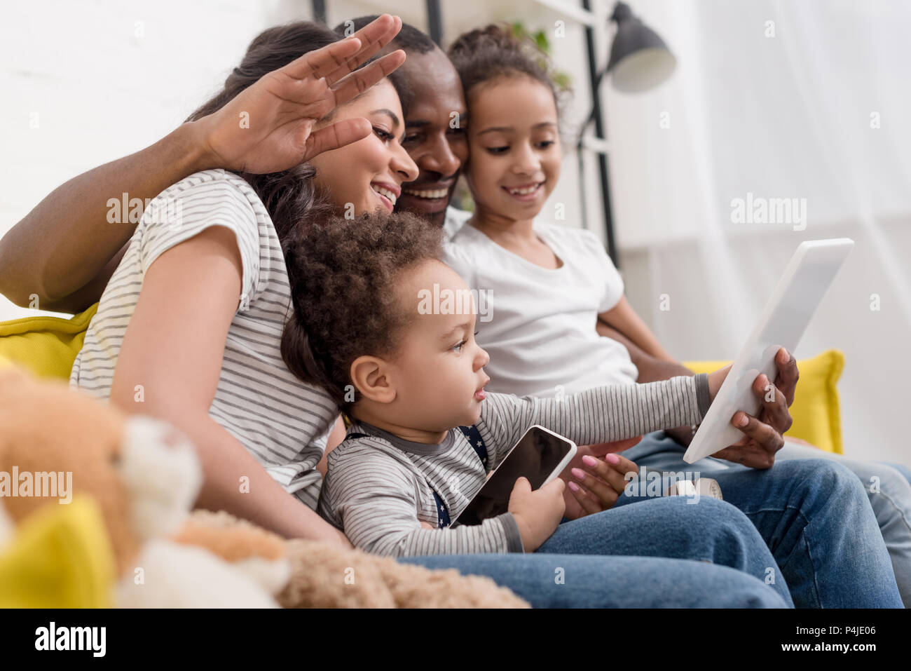 happy young family making video call with tablet at home - Stock Image