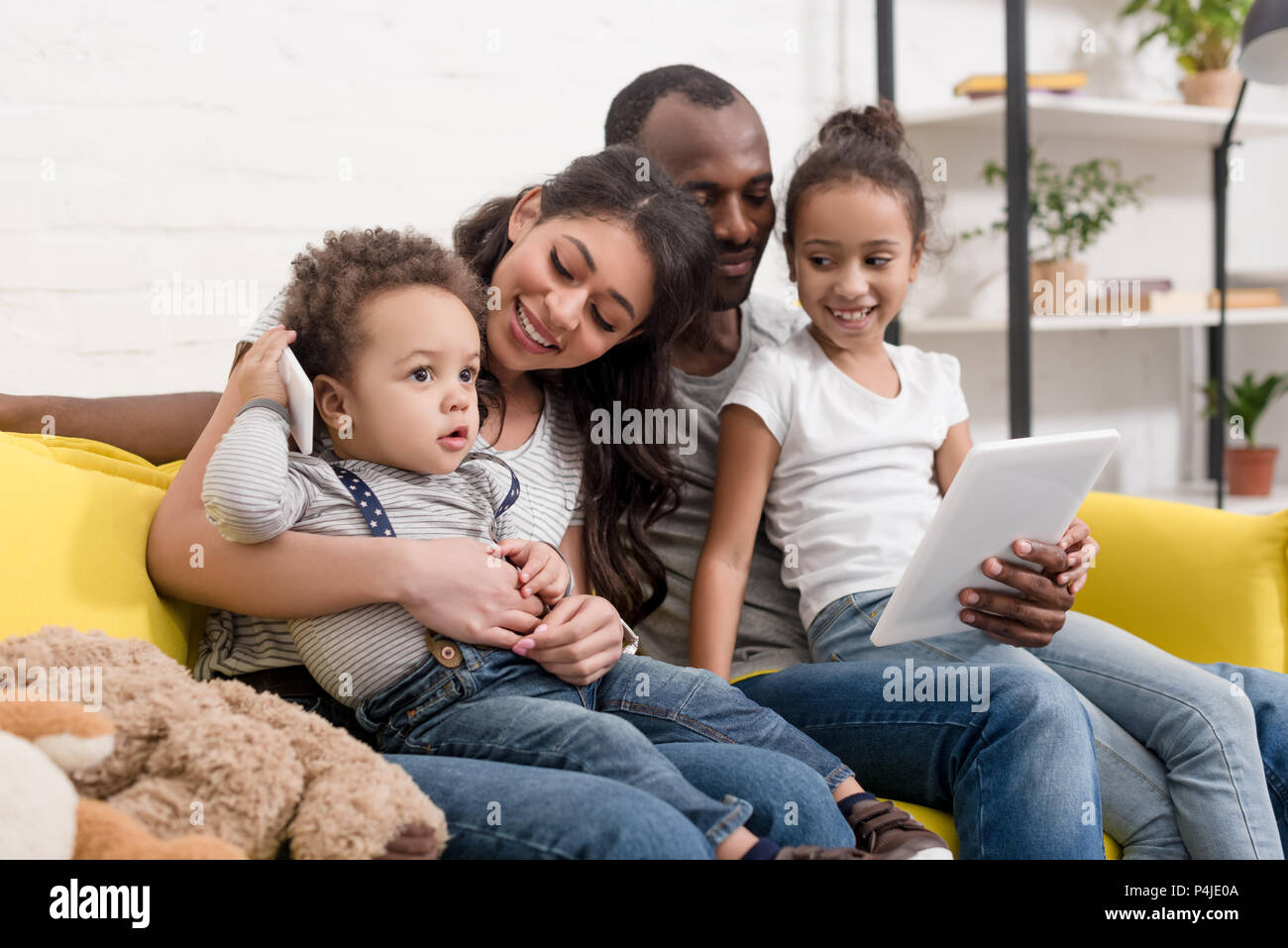 happy young family spending time together with devices at home - Stock Image