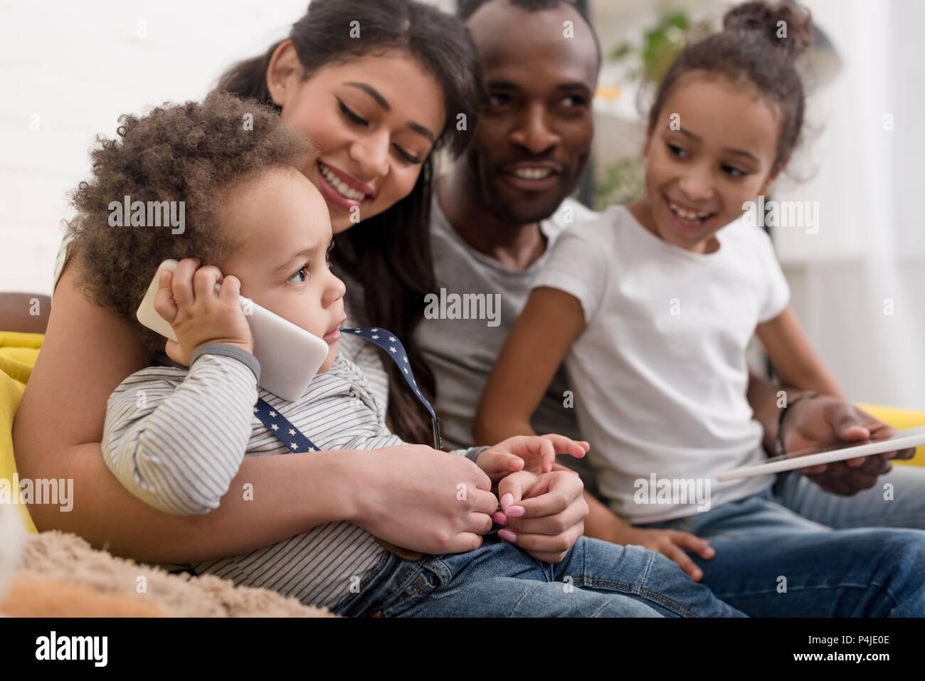 happy young family spending time together with devices - Stock Image