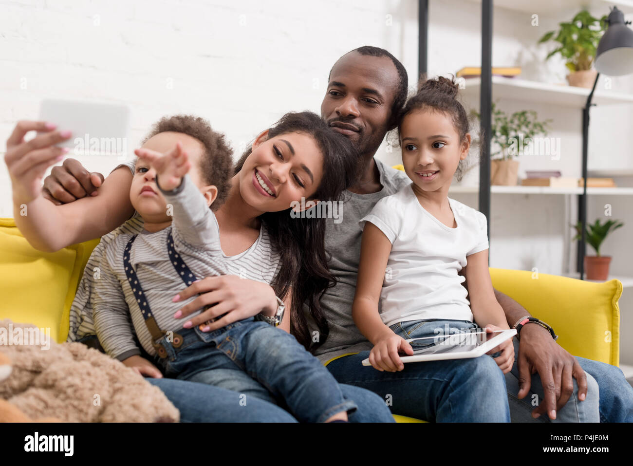 happy young family taking selfie on couch at living room - Stock Image
