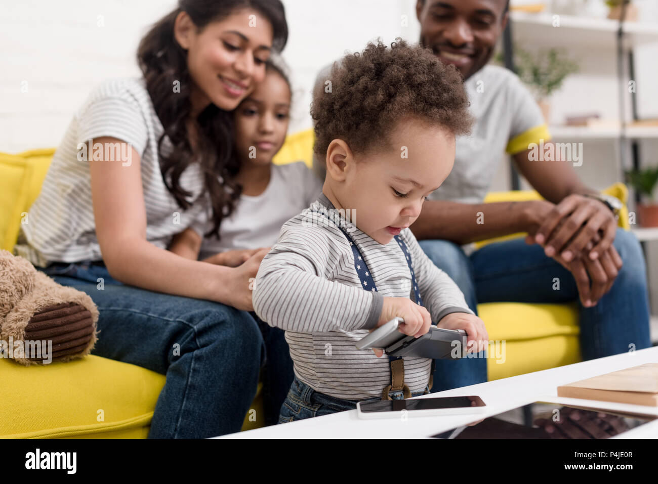 happy young family looking at son playing with gadgets - Stock Image