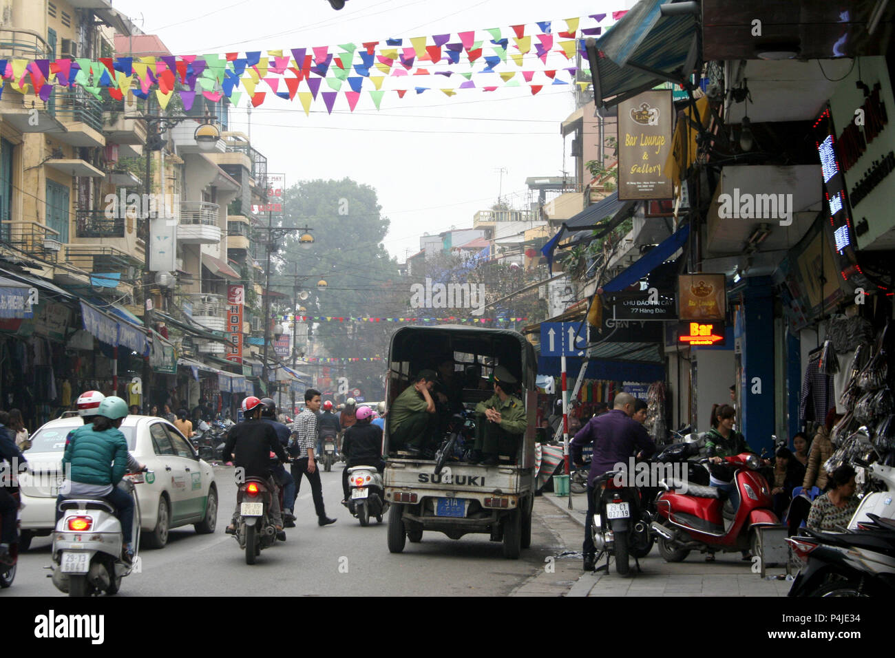 Brightly coloured bunting over busy street, Hanoi, Vietnam - Stock Image