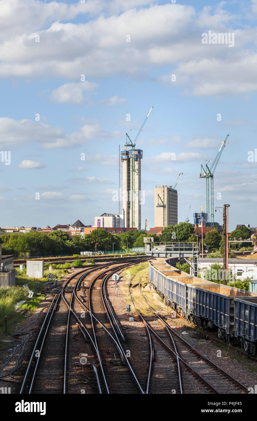 The changing skyline of Woking, Surrey: railway tracks lead into tower cranes and the new high rise Victoria Square town centre redevelopment project - Stock Image