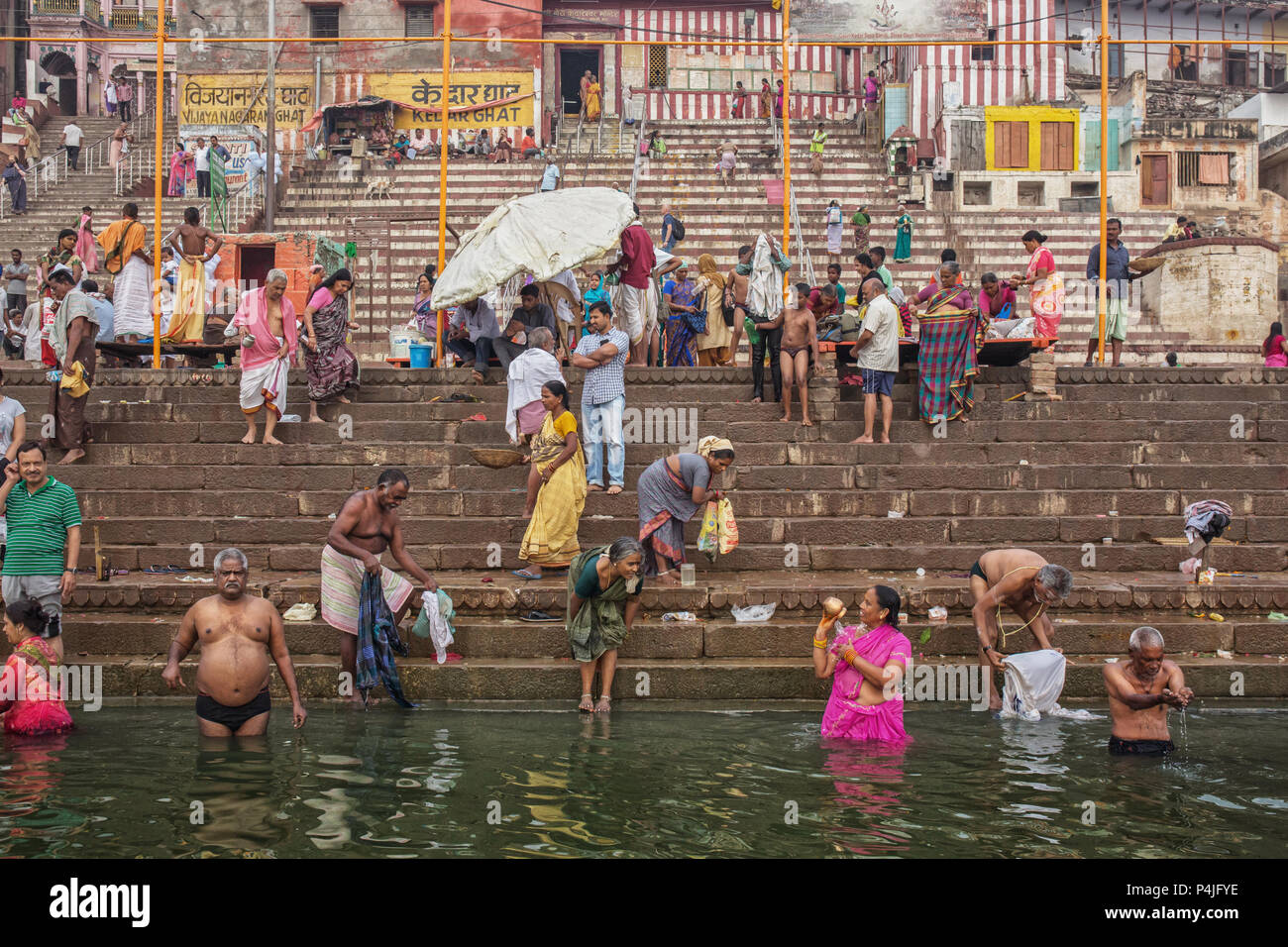 4914fa39231 men and women bathe in The Ganges River during Hindu puja, Varanasi, India.  Puja is sacred ritual for Indians and means Hindu praying