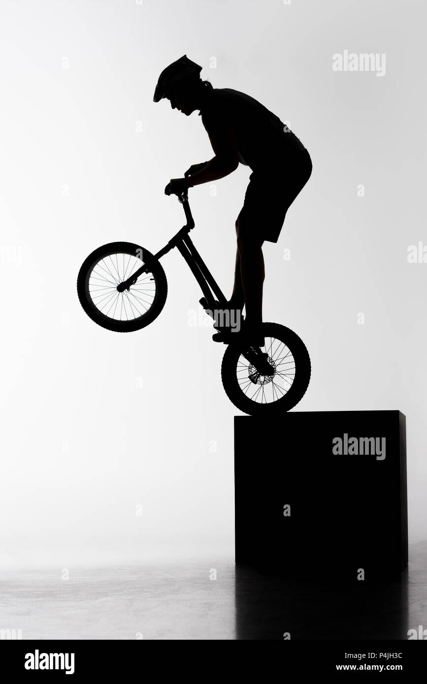 silhouette of trial biker performing stunt while balancing on cube on white Stock Photo