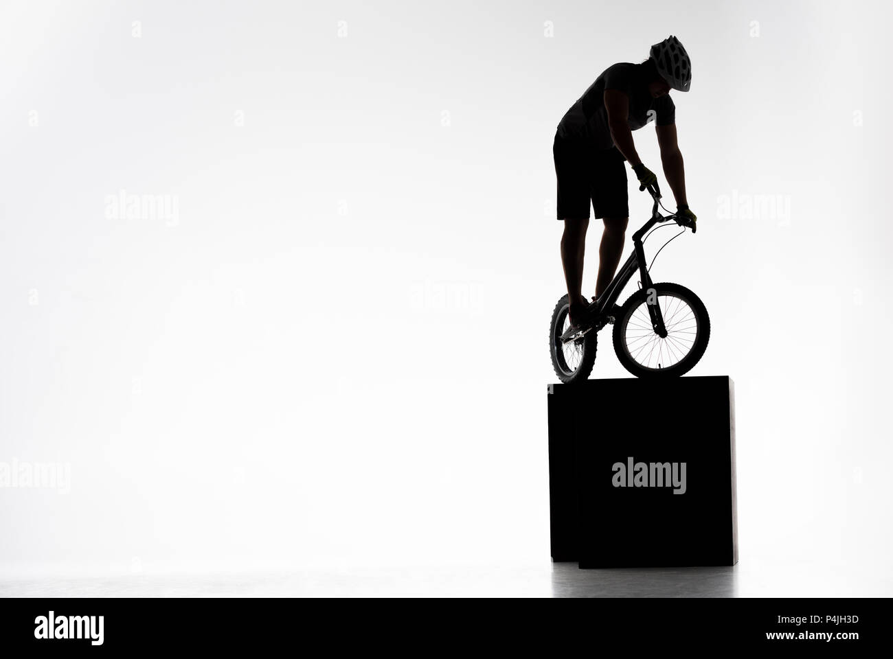 silhouette of trial cyclist balancing on obstacles on white - Stock Image