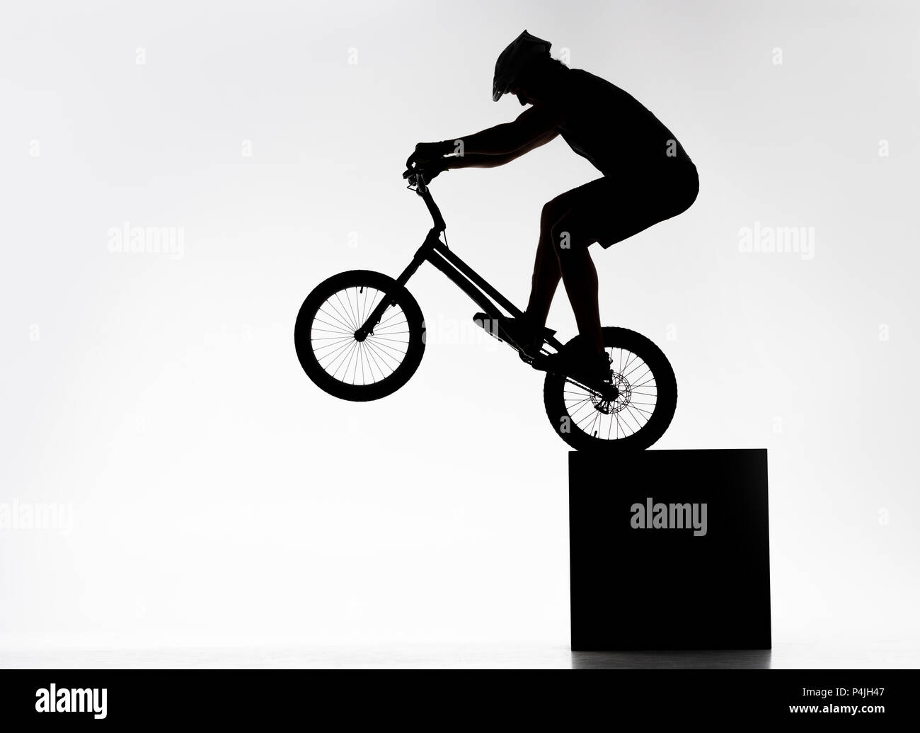 silhouette of trial cyclist performing back wheel stand while balancing on cube on white Stock Photo