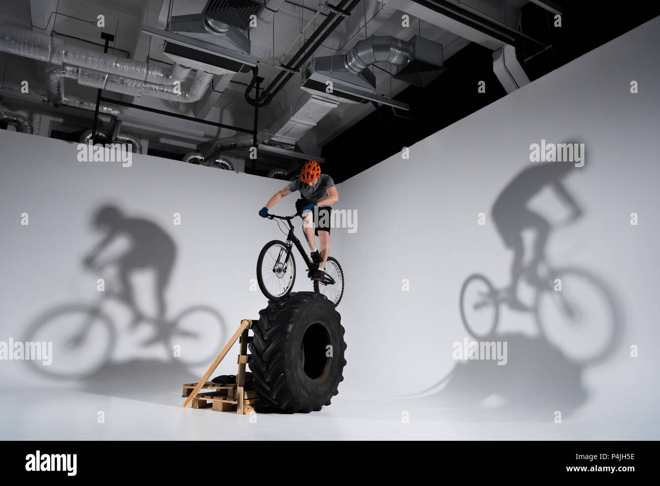 young athletic trial biker balancing on tractor wheel - Stock Image