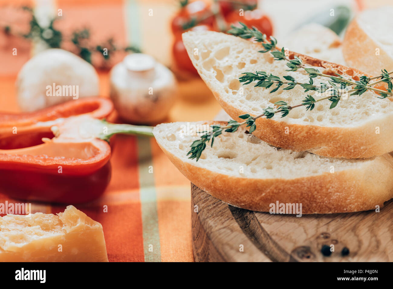 close-up view of fresh sliced baguette on wooden cutting board and parmesan cheese with bell pepper and mushrooms on table - Stock Image
