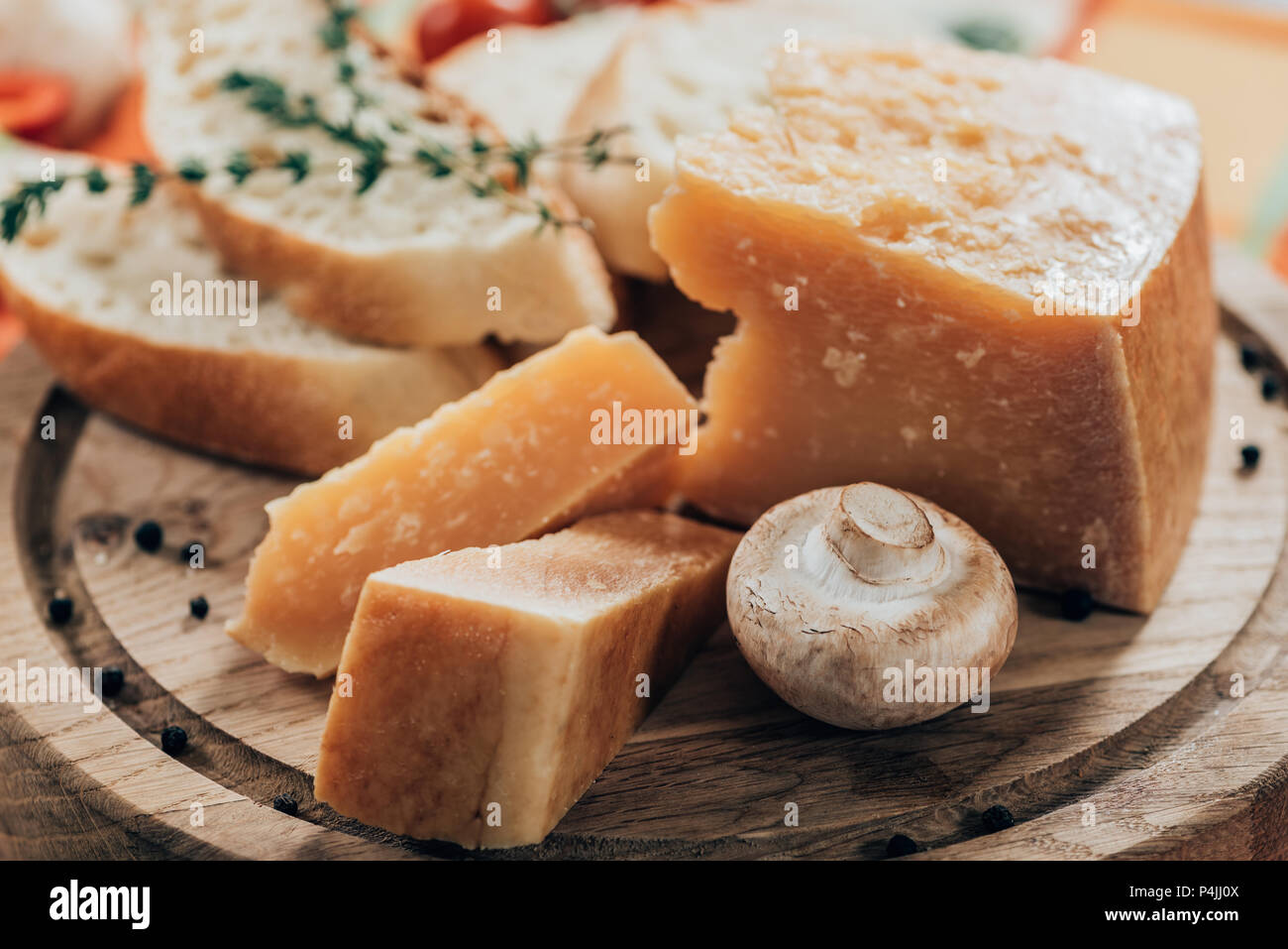close-up view of delicious baguette and parmesan cheese with mushroom on wooden cutting board - Stock Image