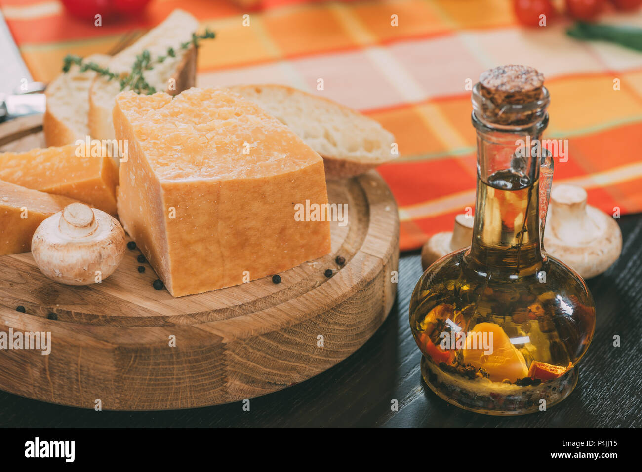 baguette and parmesan cheese on wooden cutting board and oil with spices in glass jug on table - Stock Image