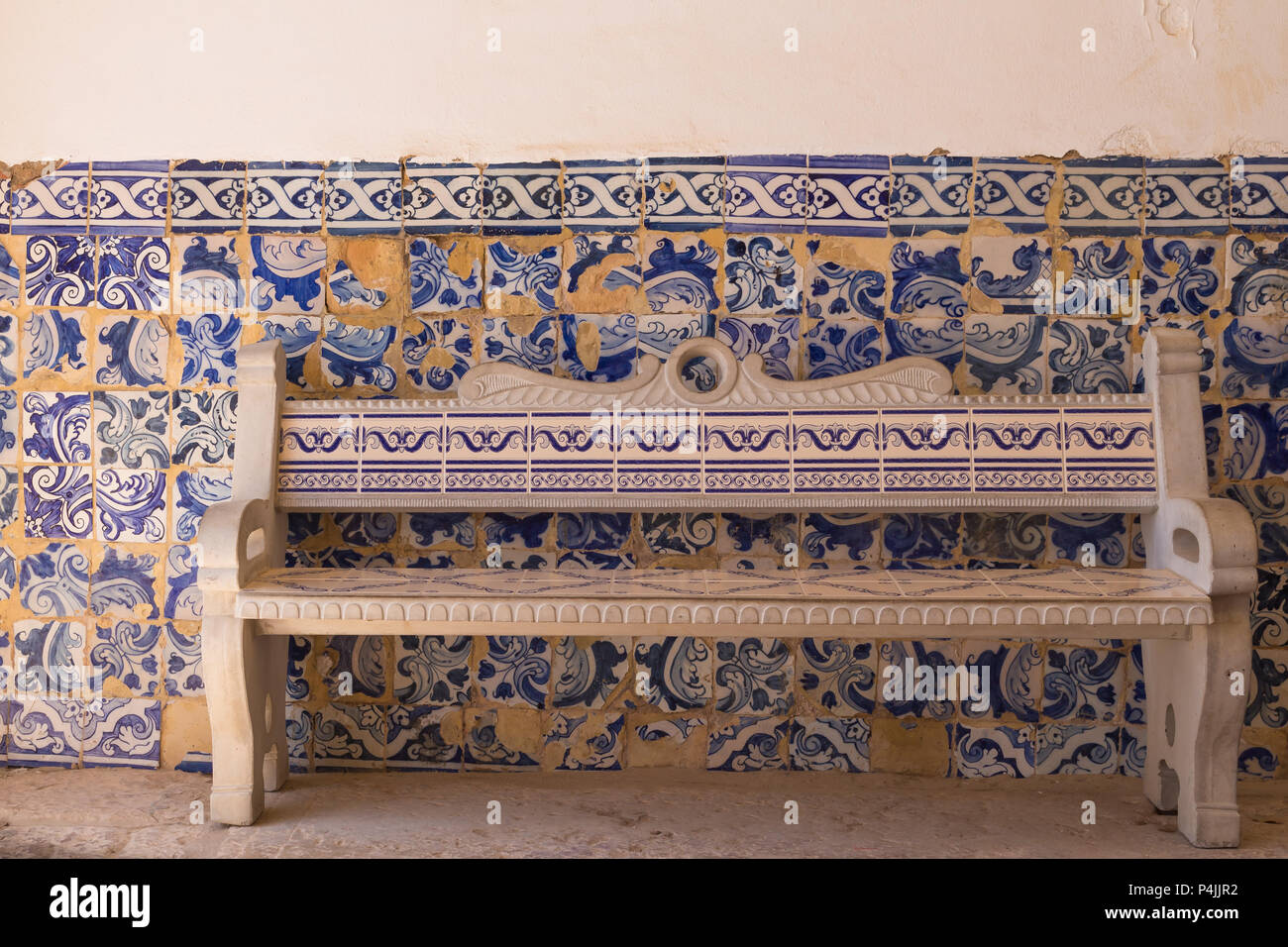 Bench and a wall with traditional ceramic azulejos, tiles with floral motives. Church of Nossa Senhora da Rocha, Algarve, Portugal. - Stock Image