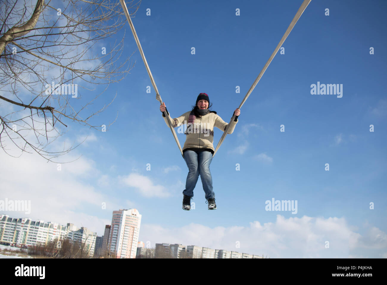 An adult woman rides high on a rope swing - Stock Image