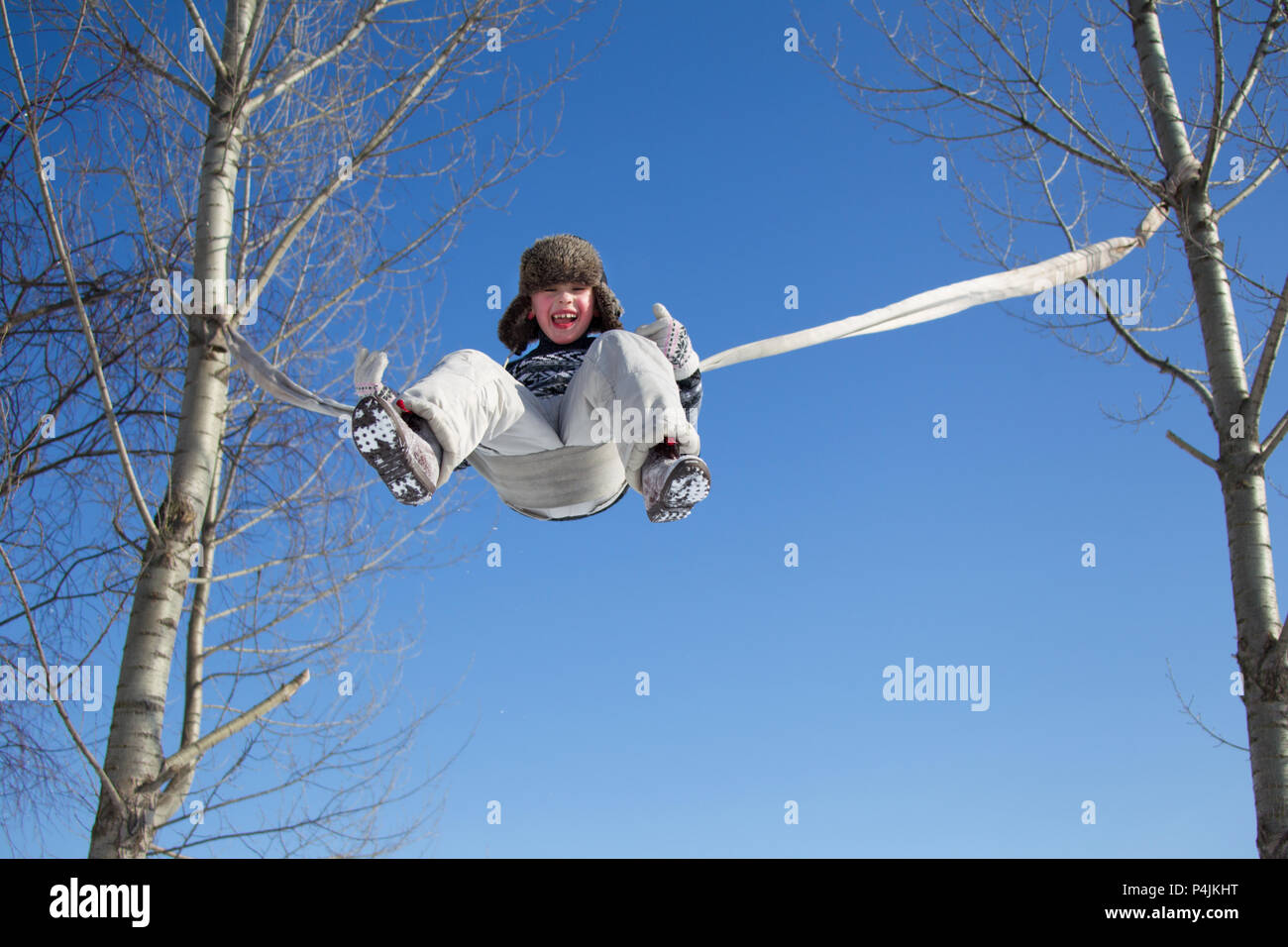 A little boy is riding a rope swing on a winter day high - Stock Image