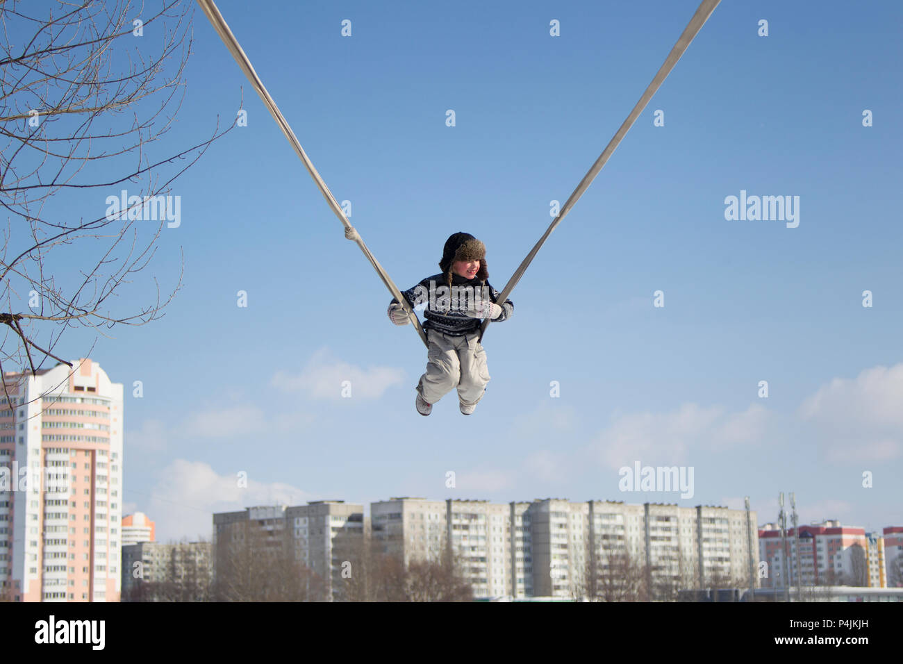 The child is riding high on a swing from the rope - Stock Image