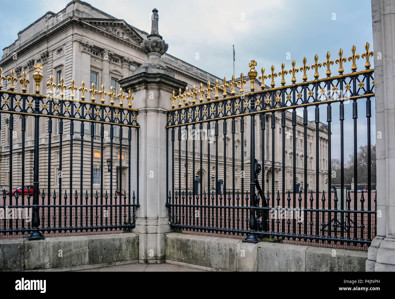 Part of the black cast-iron railings with gilded tips outside the Buckingham Palace, including the corner ashlar pier. - Stock Image