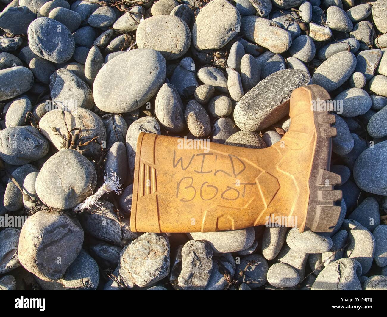 Plastic and rubbery rubbish washed up on a stony beach.  Photo showing pollution problem. Dangerous garbage ejected from the sea on remote beaches. Stock Photo