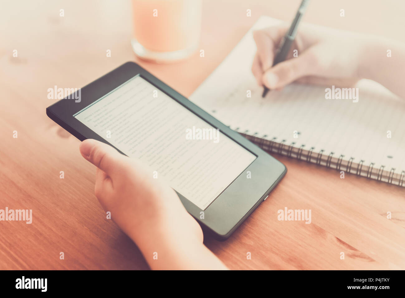 Girl is reading ebook on digital tablet device and is taking notes - Stock Image