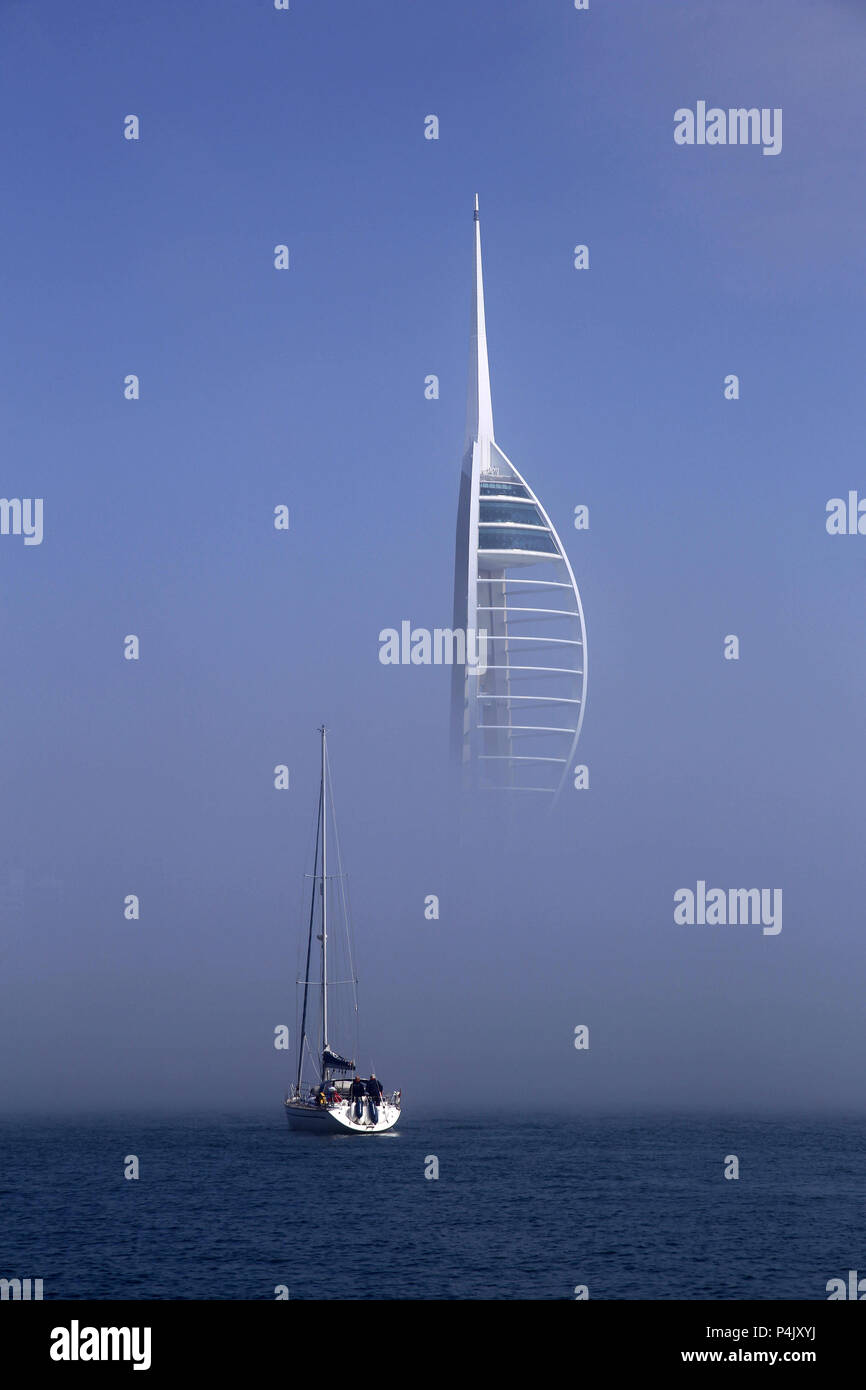 A yacht entering portsmouth harbour in fog with Spinnaker Tower in background - Stock Image